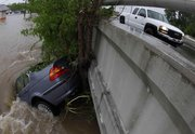 A car is pinned against a tree and a bridge Sunday in Nashville, Tenn. Severe storms dumped heavy rain on Tennessee for the second straight day, leaving at least 15 dead in Tennessee and northern Mississippi.