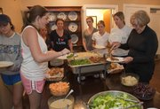 Molly McGroder, right, serves up dinner during a recent evening meal.
