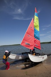 Angie and Todd Wilson of Des Moines pull in their Hobie sailboat.