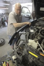 Rusty Elliott works on a car at Hite Collision Repair Center, 3401 W. Sixth St., which sees two to five vehicles a week from accidents where text messaging is involved. A Kansas University professor recently polled 400 college students and found that 95 percent of them drive and text at the same time.