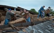 Members or the De Soto community gathered at Zimmerman's Kill Creek Farm on Friday night to help in the cleanup efforts of the White-Waitzmann Barn, which was destroyed in a storm Wednesday night.