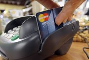 A customer swipes a MasterCard debit card through a machine while checking out at a shop Nov. 2, 2009, in Seattle. Congress may be poised to tighten restrictions on the fees that businesses pay when customers  make debit card payments.