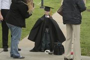 Collin Schmidt, 5, of Wichita tries on his uncle Josh Golka's graduation gown before KU's commencement ceremony Sunday at Memorial Stadium.