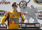 Kyle Busch poses in victory lane with the trophy after winning the NASCAR Sprint Cup Series' Autism Speaks 400 on Sunday in Dover, Del.