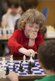 First-grader Max Chisholm, 7, hides his excitement as he makes a move against his competitor and classmate John Hauptil, 7, during a meeting of the Cordley Chess Club at Cordley School.