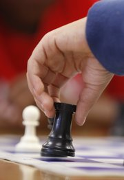 A young chess enthusiast moves a rook during practice at Cordley School.