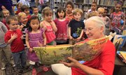 Children from Century School listen to storytime as Linda Clay, library assistant, reads aloud. Clay helped kick off the 2010 summer reading program at Lawrence Public Library.