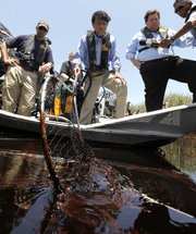 Louisiana Gov. Bobby Jindal, center, and Plaquemines Parish President Billy Nungesser, right, tour the oil-soaked marsh of Pass a Loutre, La., on Wednesday. Oil from the Deepwater Horizon oil spill is infiltrating the coast of Louisiana.