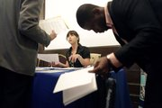 "Deji Ayoade, right, of Queens, who has been out of work for six months, looks over a list of available jobs as Jaclyn Coughlan, center, a recruitment specialist with the Visiting Nurse Service of New York, speaks to another job applicant this week during the ""Putting New Yorkers Back to Work"" Job Fair sponsored by The New York Society for Ethical Culture in New York. The number of newly laid-off workers filing claims for unemployment benefits unexpectedly rose last week to the highest level in a month."