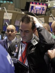 Trader Gregory Rowe, right, works Thursday on the floor of the New York Stock Exchange. The Dow Jones industrial average fell 376 points, its biggest one-day point drop since February 2009, and all the major indexes were down well over 3 percent.
