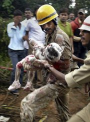 Indian firefighters carry a child, who is believed to have died, out of the debris of an Air India plane that crashed Saturday in Mangalore, in the southern Indian state of Karnataka. The plane arriving from Dubai crashed Saturday morning after it overshot a runway while trying to land in southern India, and officials feared as many as 150 people on board were killed.