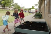 Hilltop Child Development Center students, from left, Shivani Sharma, 4; Mikaiah Barber, 4; and Luke Polonchek, 5, rake a garden bed in May 2010 to prepare it for planting.