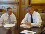 Gov. Mark Parkinson signs appropriations bill on Thursday as Lt. Gov. Troy Findley looks on.