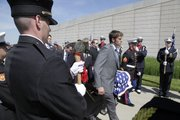 Pallbearers carry the casket of Shawnee firefighter John Glaser while an honor guard stands at attention Thursday.