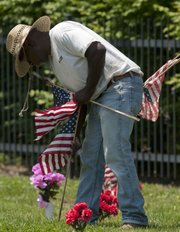 Frank Demby Jr. sets American flags Friday at headstones in the veterans plot at Oak Hill Cemetery. The Lawrence Parks and Recreation Department sets about 350 flags along with a bouquet of plastic flowers.