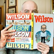 "Daniel Clowes, at his home in Oakland, Calif., shows off his latest graphic novel, ""Wilson."" It features a character who hangs around the coffee shops on Oakland's Grand Avenue, verbally sucker punching strangers with whom he instigates one-sided conversations."