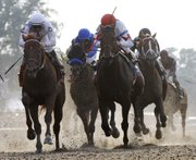 Drosselmeyer, left, approaches the finish of the 142nd Belmont Stakes. Jockey Mike Smith led the 13-to-1 underdog to victory on Saturday in Elmont, N.Y.
