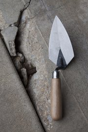 Skillful use of a trowel can make concrete used to repair cracks blend in with the existing surface.