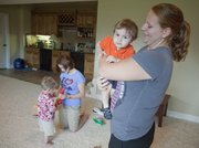 Au pair Jessica Zachmann, from Germany, takes care of Ryan Mastrosimone, 1, at the home of his mother, Gina Spade. In the background at left, Jasmin Weimer, also an au pair from Germany, plays with Luke Pape, 2.