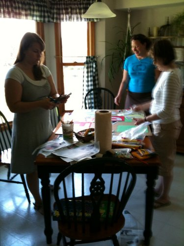 "From left, Anne Kealing, Christine Metz and Jane Stevens decorate a team banner for Relay For Life of Douglas County, which is Friday. The ""We Are the World (Co.)"" team members worked on a banner and luminarias Sunday afternoon at my house."