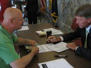 Johnson County Republican Party Chairman Ronnie Metsker (left) on Thursday provides the paperwork to file the candidacy of Mike Foltz in House District 24, now held by state Rep. Mike Slattery, a Democrat. Foltz was the last candidate to file before the deadline.