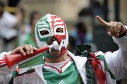 A Mexico fan blows a plastic trumpet Thursday in Johannesburg. Mexico will play South Africa in the first World Cup match at 9 a.m. today in Johannesburg.