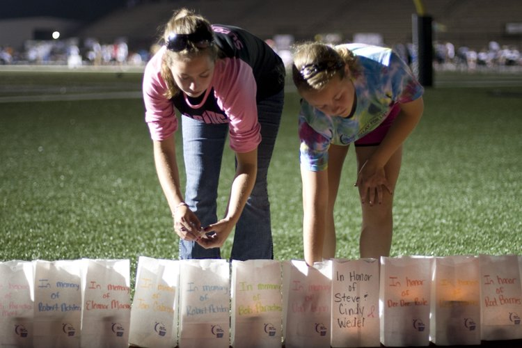 Jessie Lanzrath, left, and Baylee Parsons, from Topeka, light luminarias during the Relay For Life event. The luminarias honor people who have fought cancer.
