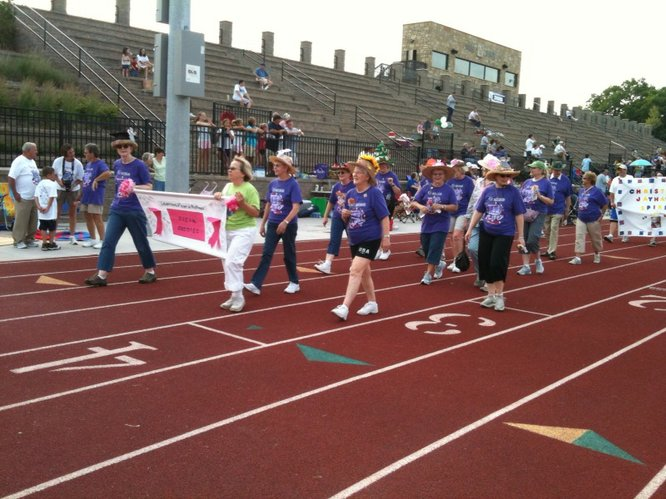 The Bosom Buddies' team makes its first lap around the track during Relay For Life of Douglas County. Bosom Buddies is a weekly breast cancer support group in Lawrence.