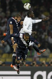 England's Emile Heskey, top right, vies for the ball with United States' Oguchi Onyewu, left, and United States' Ricardo Clark during the World Cup Group C soccer match. The United States tied England, 1-1, on Saturday in Rustenburg, South Africa.