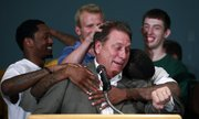 Michigan State basketball coach Tom Izzo, center, is hugged by players, including Kalin Lucas, left, Austin Thornton, center rear, Korie Lucious, right front, and Garrick Sherman, right rear, during a news conference Tuesday in East Lansing, Mich.
