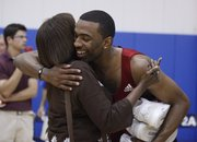Keith Langford, right, gives a hug to former teammate Jeff Hawkins' mother, Addye Hawkins, following an alumni scrimmage on June 16 at Horejsi Center. Langford, 26, plays for Khimki Moscow in the Euroleague.