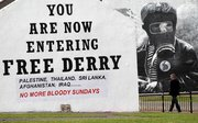 A man walks past a Bloody Sunday mural Tuesday in the Bogside area of Londonderry, Northern Ireland.