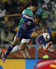 Mexico's Francisco Javier Rodriguez, back, competes for the ball with France's Florent Malouda during the World Cup Group A soccer match Thursday at Peter Mokaba Stadium in Polokwane, South Africa. Mexico knocked off France, 2-0, to move to 1-0-1 in group play. France fell to 0-1-1.