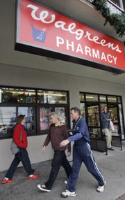 In this file photo taken Dec. 17, 2007, people walk past a Walgreens Pharmacy in San Francisco. CVS Caremark Corp. and Walgreen Co. have settled a dispute Friday, June 18, 2010, that threatened to change where millions of Americans fill prescriptions.