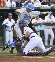 UCLA's Beau Amaral (25) is tagged out at home plate by Florida catcher Mike Zunino in the first inning of the second game of the College World Series. UCLA won, 11-3, Saturday in Omaha, Neb. See story Page 2C.
