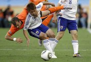 Japan's Yuichi Komano, center, is tackled by Netherlands' Rafael van der Vaart, left, during the World Cup group E soccer match Saturday in Durban, South Africa. The Netherlands won, 1-0.