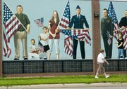 An unidentified person walks past a patriotic mural in Fremont, Neb., in this photo taken Saturday. Fremont voters on Monday approved a measure to ban hiring of or renting property to illegal immigrants.