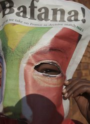 A child peers through a newspaper front page as patrons gathered to cheer on South Africa in the World Cup. South Africa beat France, 2-1, on Tuesday in Bloemfontein, South Africa, but failed to qualify for the next round.