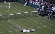 John Isner of the U.S., left, smiles at Nicolas Mahut of France as he lies on the court on Wednesday at Wimbledon.