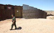 U.S. Border Patrol agent Santos Flores walks in front of the old border fence, back left, where it meets a five mile section of new border fence at the border in Nogales, Ariz., in this June 19, 2008, file photo. President Barack Obama's plan to hire 1,000 more Border Patrol agents and other immigration officers could end up flooding the U.S.-Mexico border's already overwhelmed federal courts, a judiciary official said Friday.
