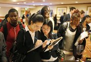 Flora Guan, left, and Jessica Yang, right, recent graduates of San Francisco State University, fill out forms to take part in surveys with Fieldwork San Francisco on June 28 at a National Career Fair in San Francisco. The unemployment rate fell to 9.5 percent, its lowest level in almost a year.