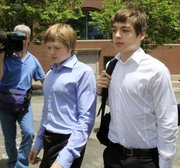 Tim Foley, 20, left, and his brother Alex, 16, leave federal court Thursday after a bail hearing for their parents, Donald Heathfield and Tracey Lee Ann Foley, in Boston, who are among 11 people accused of trying to infiltrate U.S. policymaking circles.
