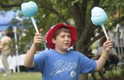 Jacob Holiday, Lawrence, holds up some cotton candy for sale on Sunday. People gathered in Watson Park on Sunday afternoon to enjoy food from the Lawrence Originals and other activities.