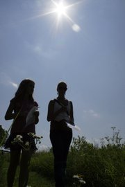 Melissa Anderson, left and Paige Bellmyer, 11, participate in a scavenger hunt for prairie plants during an event June 26 at the Guess Prairie northwest of Lawrence. The event for Big Brothers Big Sisters participants was sponsored by the Grassland Heritage Foundation.