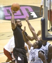 NBA free-agent LeBron James, black shirt, takes a shot over Florida State defender Chris Singleton (36) during a scrimmage at the LeBron James Skills Academy on Monday in Akron, Ohio.