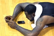 LeBron James works on one of his BlackBerry devices after the evening workout with high school basketball players at his skills academy on Tuesday in Akron, Ohio.