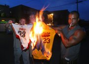Cleveland Cavaliers fans, from left, Josh Hall, Rob Hose, and Mike Adams set fire to LeBron James jerseys on Thursday in Akron, Ohio, after James announced he is leaving the Cavaliers to join the Miami Heat.