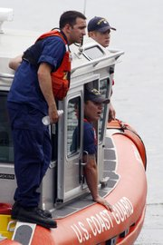Members of the Coast Guard look Thursday for two missing tour boat passengers on the Delaware River in Philadelphia. The passengers' amphibious craft in which they were riding was struck and sunk by a barge Wednesday.