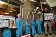 Labor activists throw paper money in front of paper figures representing Chinese employees of Foxconn Technology Group outside the Foxconn office in Hong Kong in this file photo taken May 25. Factory workers demanding better wages and working conditions are hastening the eventual end of an era of cheap costs that helped make southern coastal China the world's factory floor.