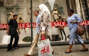 Shoppers leave an H&M clothing store Thursday in New York. Stores steepened discounts more than planned in June to help drive recession-scarred customers into the malls to buy summer merchandise. But shoppers spent cautiously amid escalating job worries, resulting in modest gains for many merchants.